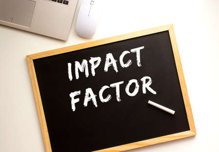 Text IMPACT FACTOR written in chalk on a slate board. Office desk. Business concept.