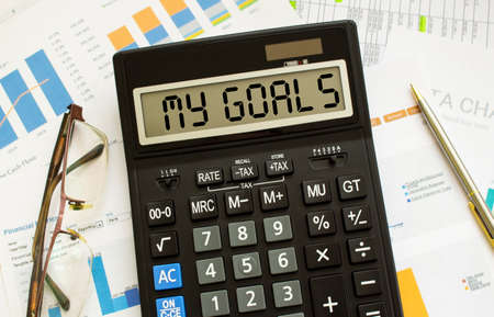 A calculator labeled MY GOALS lies on financial documents in the office. Business concept. Banco de Imagens