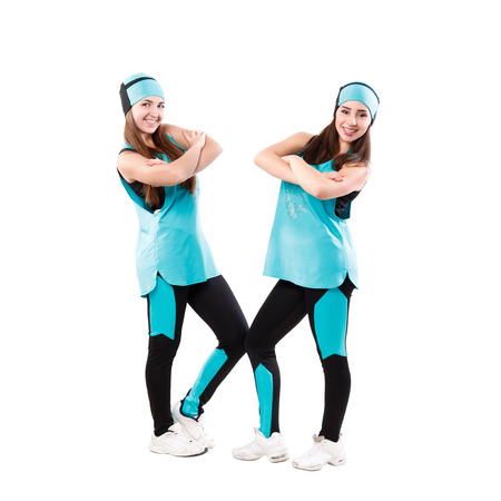 cheer full: Two young professional cheerleaders posing at studio. Isolated over white. Stock Photo
