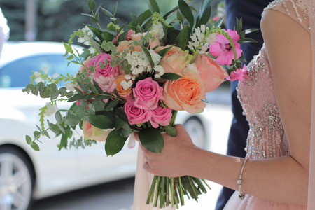 Beautiful bridal bouquet in hands of the bride. Wedding bouquet of peach roses by David Austin,  single-head pink rose aqua, eucalyptus, ruscus, gypsophila Stock Photo