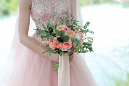 Bride holding a beautiful bridal bouquet. Wedding bouquet of peach roses by David Austin,  single-head pink rose aqua, eucalyptus, ruscus, gypsophila