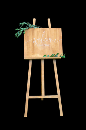 welcom: Wooden easel with a board. On the board written white paint - Welcome. Isolation on a black background