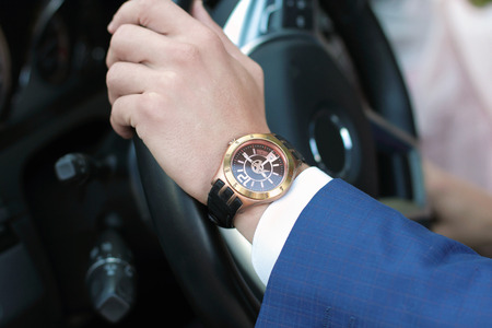 Businessman driving his car, hand on the steering wheel. Hand with golden watch. Business concept.