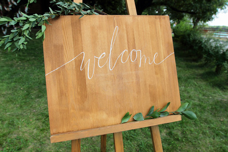 welcom: Wooden easel with a board. On the board written white paint - Welcome