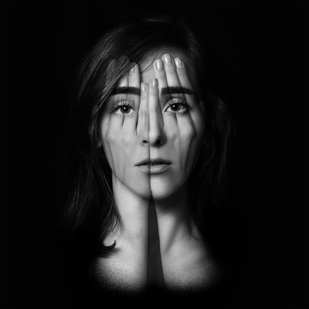 falsehood: Surreal portrait of a young girl covering  her face and eyes with  her hands.Double exposure. Black and White. Stock Photo
