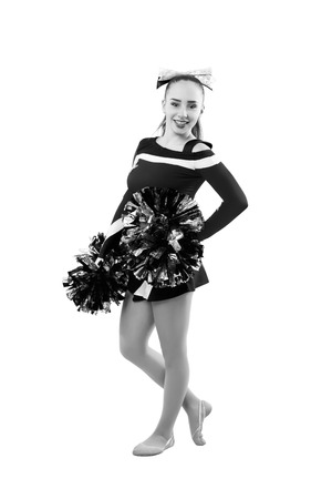 black cheerleader: young professional cheerleader with pom-pom in your hand posing at studio. Isolated over white. Black and white photography