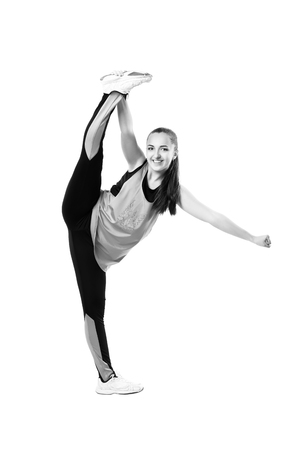 cheer full: Young professional cheerleader  stands in vertical splits. Isolated over white. Black and white photography Stock Photo