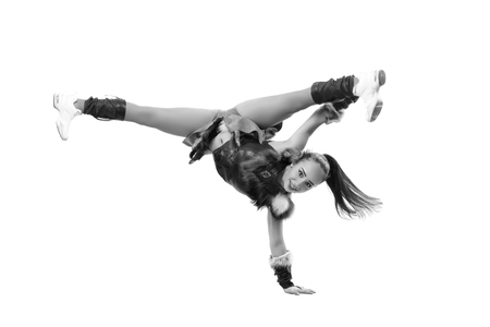 black cheerleader: Young professional cheerleader dressed in a warrior costume standing on one hand. Horizontal splits. Black and white photography