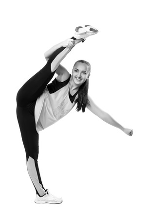 splits: Young professional cheerleader  stands in vertical splits. Isolated over white. Black and white photography Stock Photo