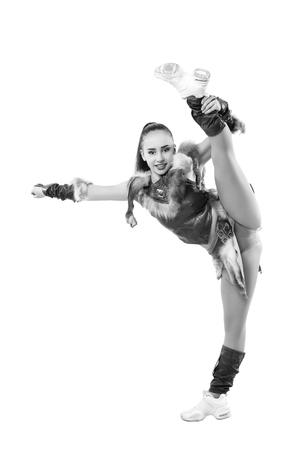 black cheerleader: Young professional cheerleader dressed in a warrior costume  standing on one leg . Vertical splits. Black and white photography Stock Photo