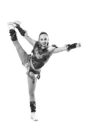 splits: Young professional cheerleader dressed in a warrior costume  standing on one leg . Vertical splits. Black and white photography Stock Photo