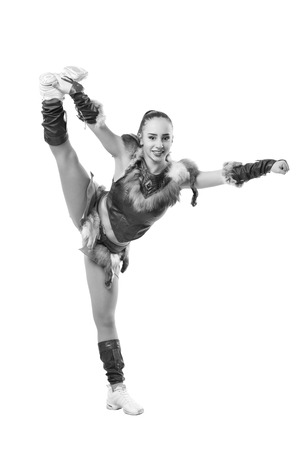 Young professional cheerleader dressed in a warrior costume; standing on one leg . Vertical splits. Black and white photography Stock Photo