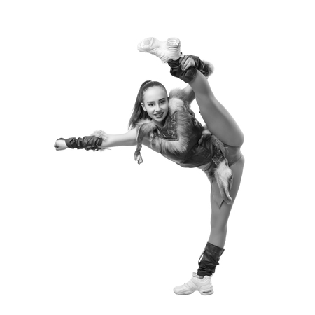 black cheerleader: Young professional cheerleader dressed in a warrior costume; standing on one leg . Vertical splits. Black and white photography Stock Photo