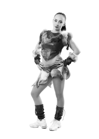 pom: Young professional cheerleader dressed in a warrior costume posing at studio. Isolated over white. Black and white photography