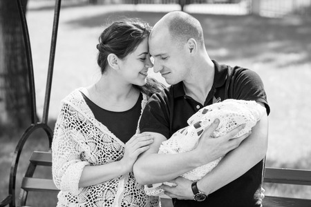 Happy family resting in a park. Father holding newborn daughter in her arms.Black and white photography