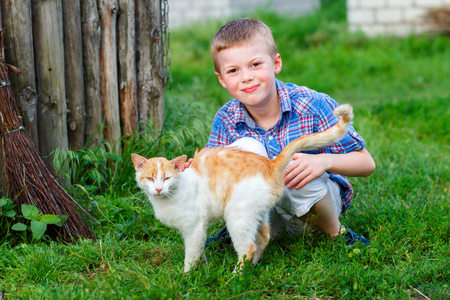 stroked: portrait of a smiling little boy in a plaid shirt with a red cat, the boy stroked the cat, the cat arched his back and closed his eyes in pleasure