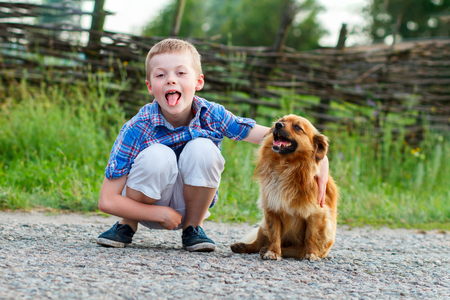 child in a plaid shirt hugs a small fluffy dog, a little boy having fun and showing tongue Stock Photo