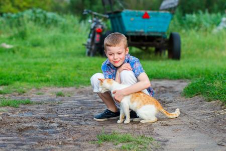 amigos abrazandose: niño juega con un gato rojo en el patio de una casa de campo