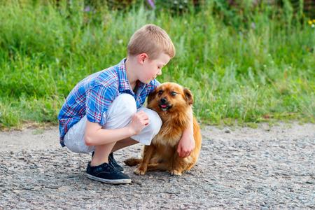 plaid shirt: little boy in a plaid shirt hugs a red dog. Best friends
