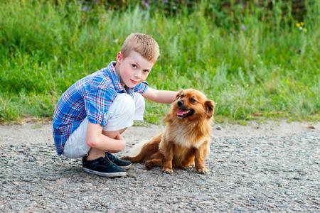 plaid shirt: boy in a plaid shirt hugging a red fluffy dog. Best friends. Outdoor