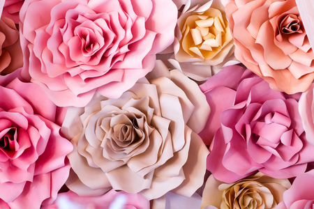 Colorful flowers paper background. Red, pink, purple, brown, yellow and peach handmade paper roses Standard-Bild