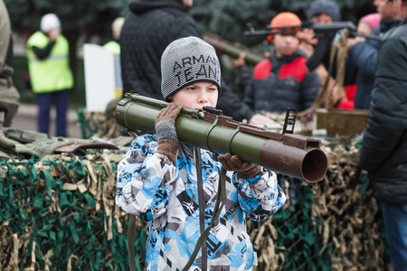 Dneprodzerzhinsk, Ukraine - October 15, 2016: child holding anti-tank rocket propelled grenade launcher Editorial