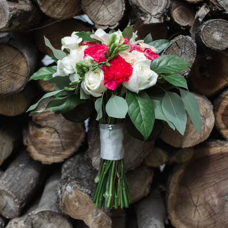Wedding bouquet of roses, freesias and carnations on a background of wood
