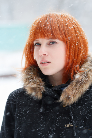 Winter portrait of a cute red-haired girl with a defiant look in a black jacket with fur during a snowstorm, red-haired woman stands in the street during a heavy snowfall, look at the camera