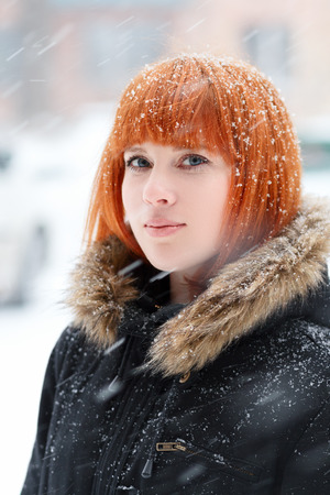 heavy snow: Winter portrait of a cute red-haired girl with blue eyes in a black jacket with fur during a snowstorm,  red-haired woman stands in the street during a heavy snowfall, look at the camera, vertical Stock Photo