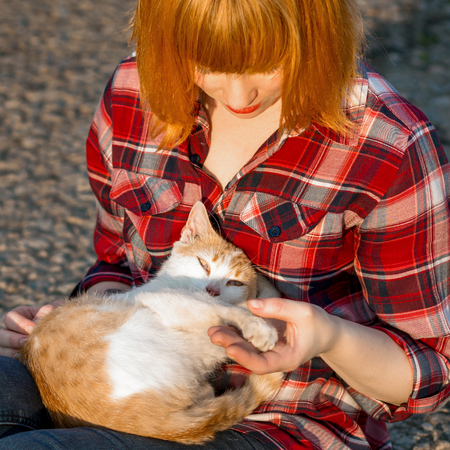 Redhead girl in a plaid shirt holding a cat in her arms, a cat curled up and looking at the camera