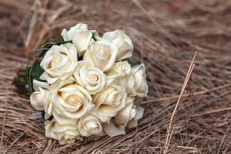 Bridal bouquet of white roses on a faded grass
