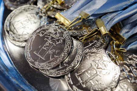 first day: Many silver medals with blue ribbons on a silver tray, awards of champions, sport achievements, second place, prize for the winner Stock Photo