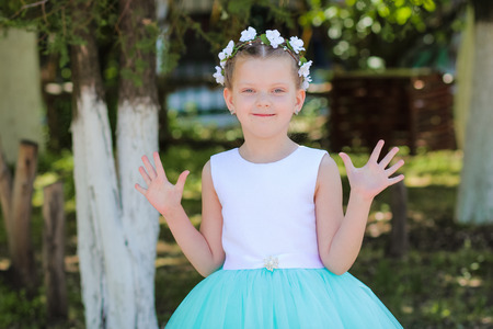he said: Small cute girl in a blue and white dress  raises his hands, he said - hello, child with a wreath of artificial flowers on her head Stock Photo