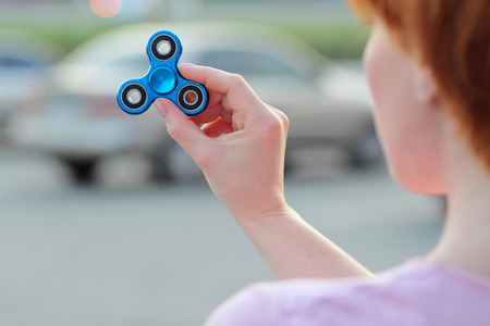 girl in pink t-shirt is playing blue metal spinner in hands on the street, woman playing with a popular fidget spinner toy, anxiety relief toy, anti stress and relaxation fidgets