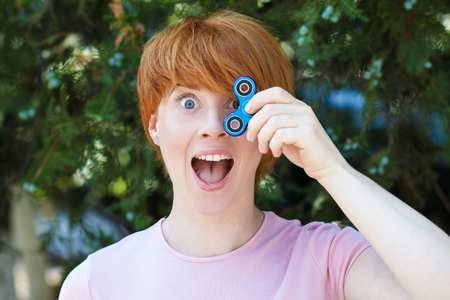 smilling girl in pink t-shirt is playing blue metal spinner in hands on the street, woman playing with a popular fidget spinner toy, anxiety relief toy, anti stress and relaxation fidgets