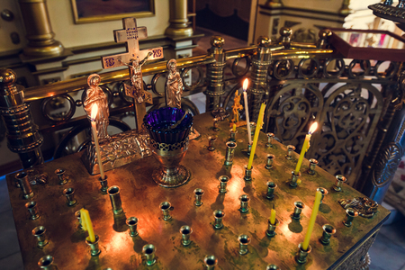 stand for candles in the interior of orthodox church, golden candleholder in church,orthodox icon lamp, church oil, church attribute, symbolic  gold cross with the crucifixion of Jesus