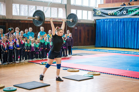 Kamenskoye, Ukraine - March 9, 2017: indicative performance of weightlifters at the championship in cheerleading,young girl lifts a heavy barbell, barbell weight - 60 kg