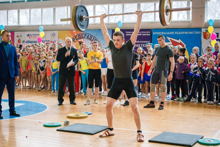 Kamenskoye, Ukraine - March 9, 2017: indicative performance of weightlifters at the championship in cheerleading, young man lifts a heavy barbell, barbell weight - 80 kg