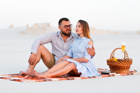 Lovely attractive couple sitting together on the white sand beach, happy couple enjoying picnic on the beach and have good time on summer vacations