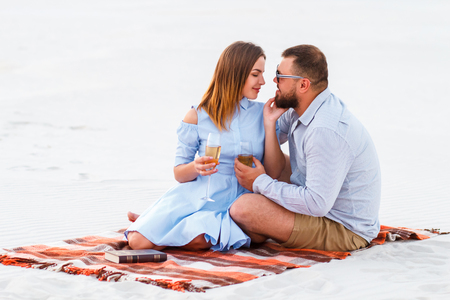 couple in love drinking wine during romantic dinner on the beach, young couple kissing and holding glasses in hands