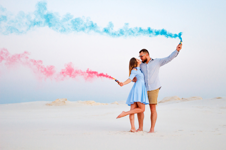 young couple kissing and holding colored smoke in hands, romantic couple with blue color and red color smoke bomb on beach Archivio Fotografico