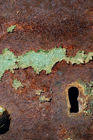 texture of rusty iron, cracked green paint on an old metallic surface, metal surface with a bolt and a keyhole