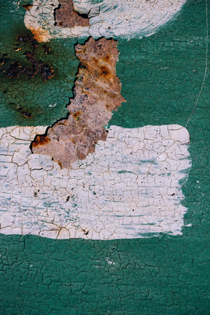 Rusty metal surface with cracked green paint, abstract rusty metal texture, green rusty metal background with a strip of white paint in the center, decay steel, decay.