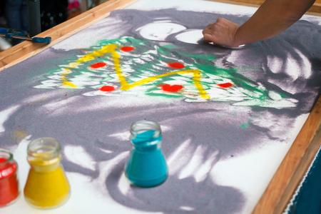 Sand animation, drawing sand closeup, girl draws a Christmas tree on the sand  Stock Photo