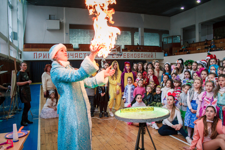 Kamenskoye, Ukraine - December 26, 2016: Christmas party for federation of cheerleading in Kamenskoye, fire show, woman in the form of a Snow Maiden blows soap bubbles, show of soap bubbles