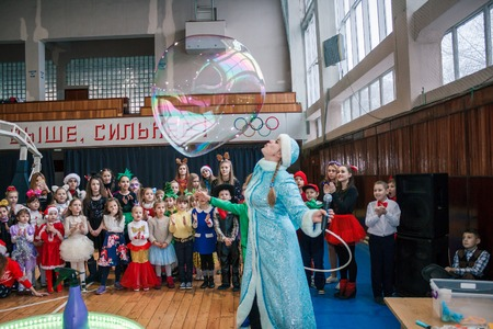 Kamenskoye, Ukraine - December 26, 2016: Christmas party for federation of cheerleading in Kamenskoye, woman in the form of a Snow Maiden blows soap bubbles, a show of soap bubbles Editorial