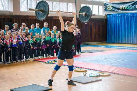 Kamenskoye, Ukraine - March 9, 2017: indicative performance of weightlifters at the championship in cheerleading,young girl lifts a heavy barbell, barbell weight - 50 kg