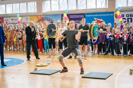 Kamenskoye, Ukraine - March 9, 2017: indicative performance of weightlifters at the championship in cheerleading, young man lifts a heavy barbell, barbell weight - 100 kg