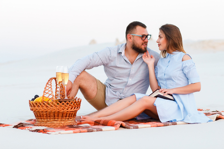 attractive couple sitting together on the white sand beach, looking each other, happy couple enjoying picnic on the beach and have good time on summer vacations, happy couple sitting on a blanket