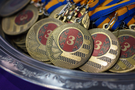 Many bronze medals with copper ribbons and yellow- blue ribbons on a silver tray, Champions awards, achievements in sport, the third place prize for the winner Stock Photo